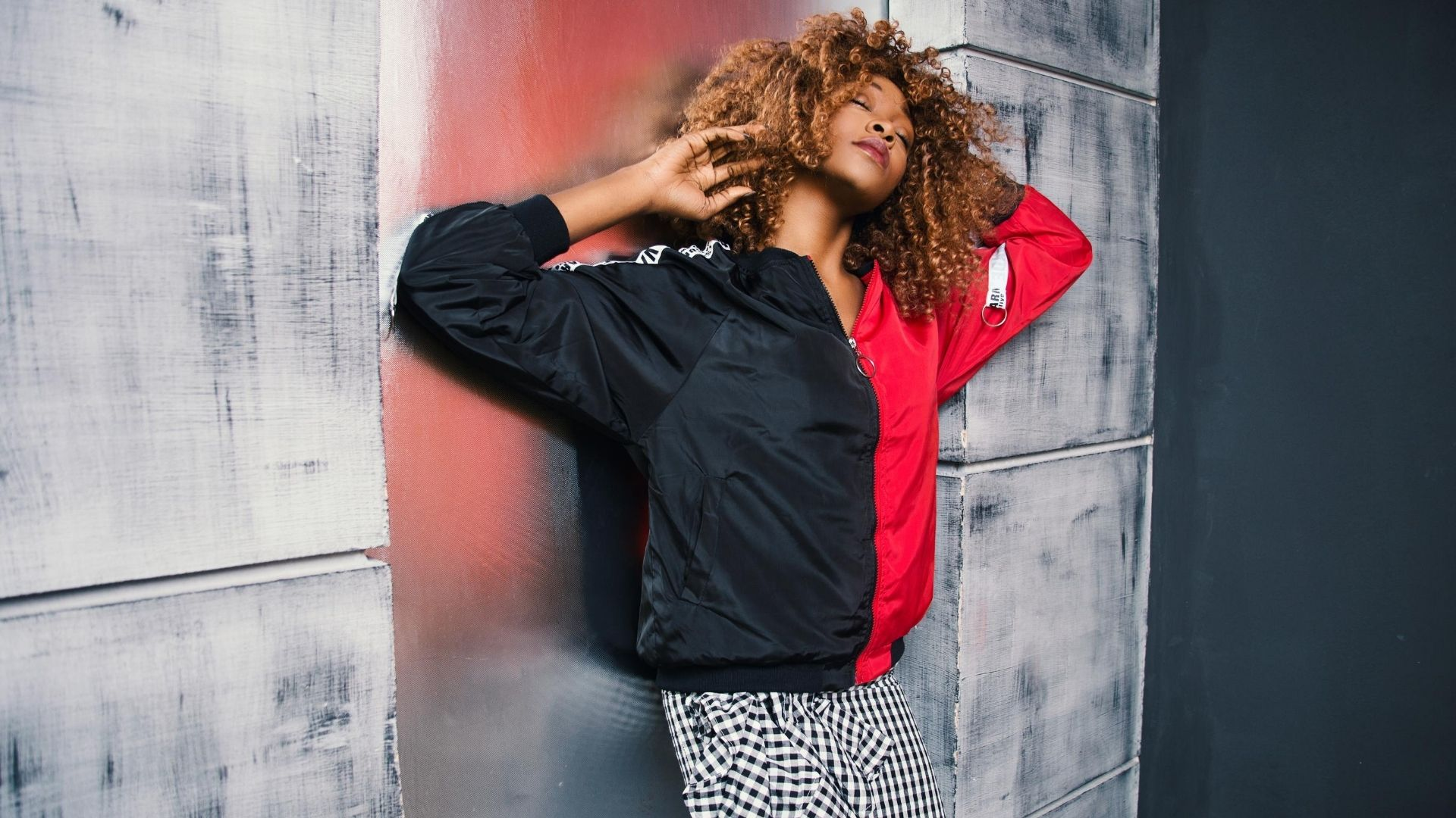 Woman wearing a black and red bomber jacket leans against a wall.