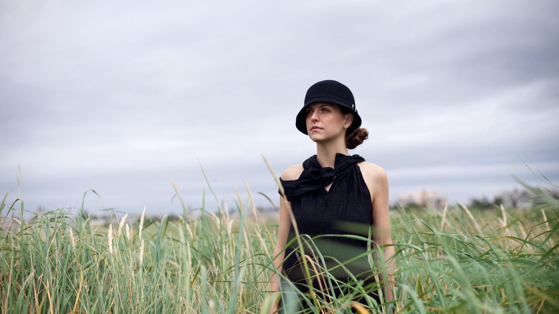 Woman in a black dress wearing a black cloche hat in an open field of grass.