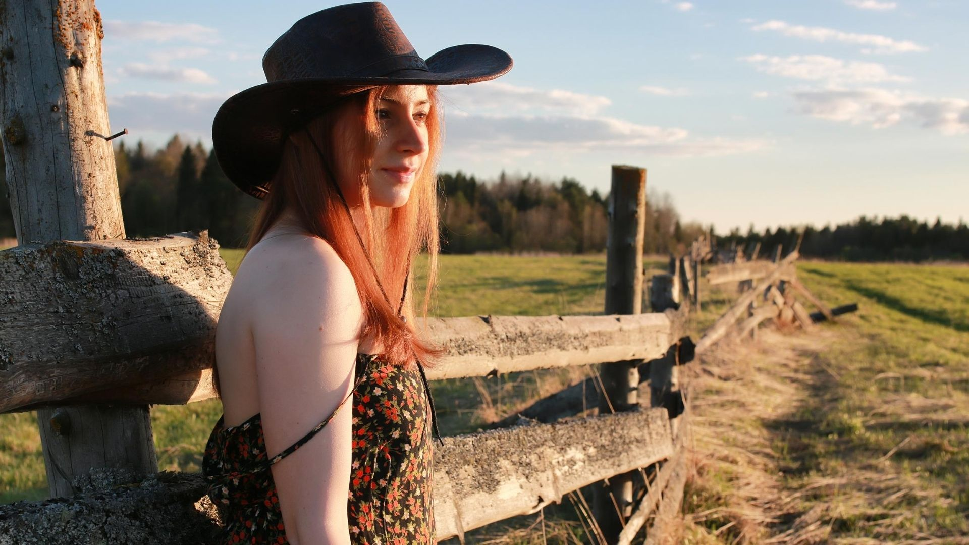 Woman wearing a black cowgirl hat.