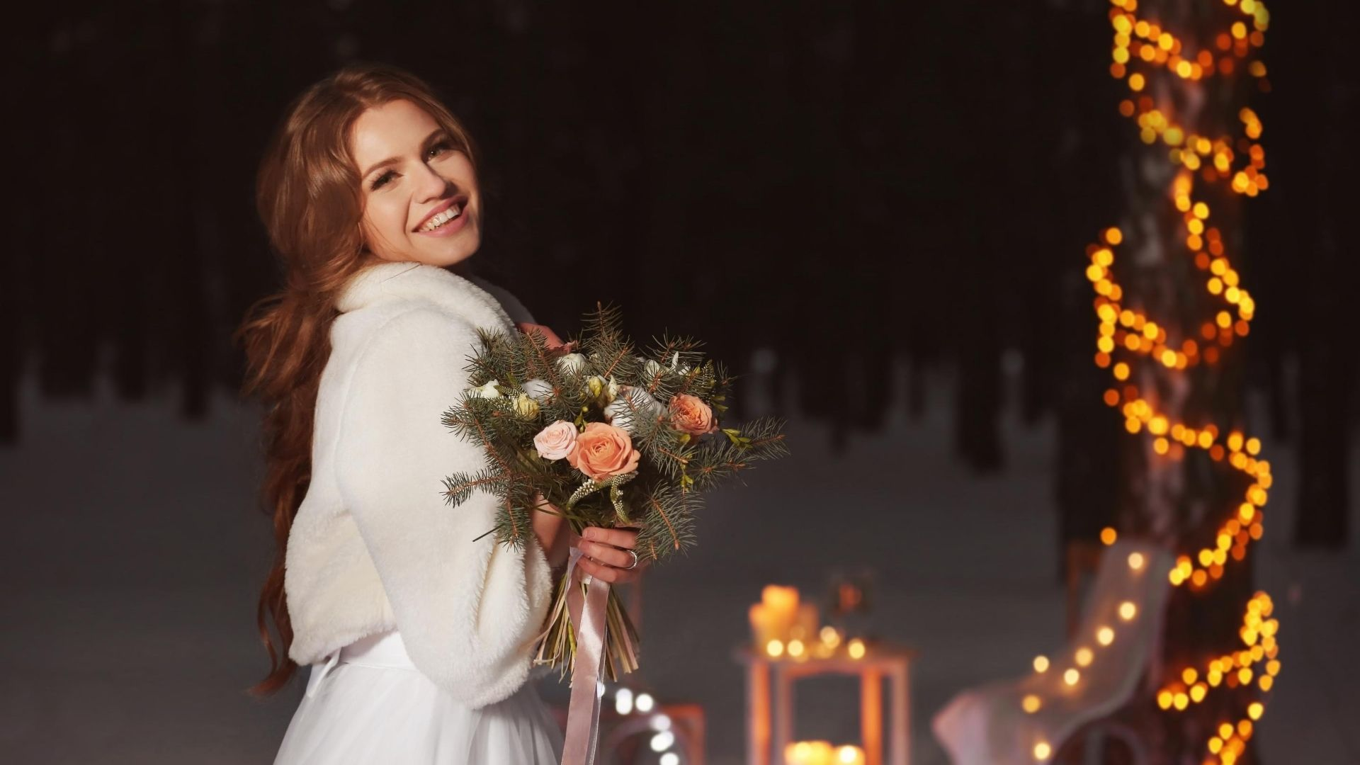 Woman wearing a fur evening coat over a hite dress holding a bouquet of flowers in her hand.