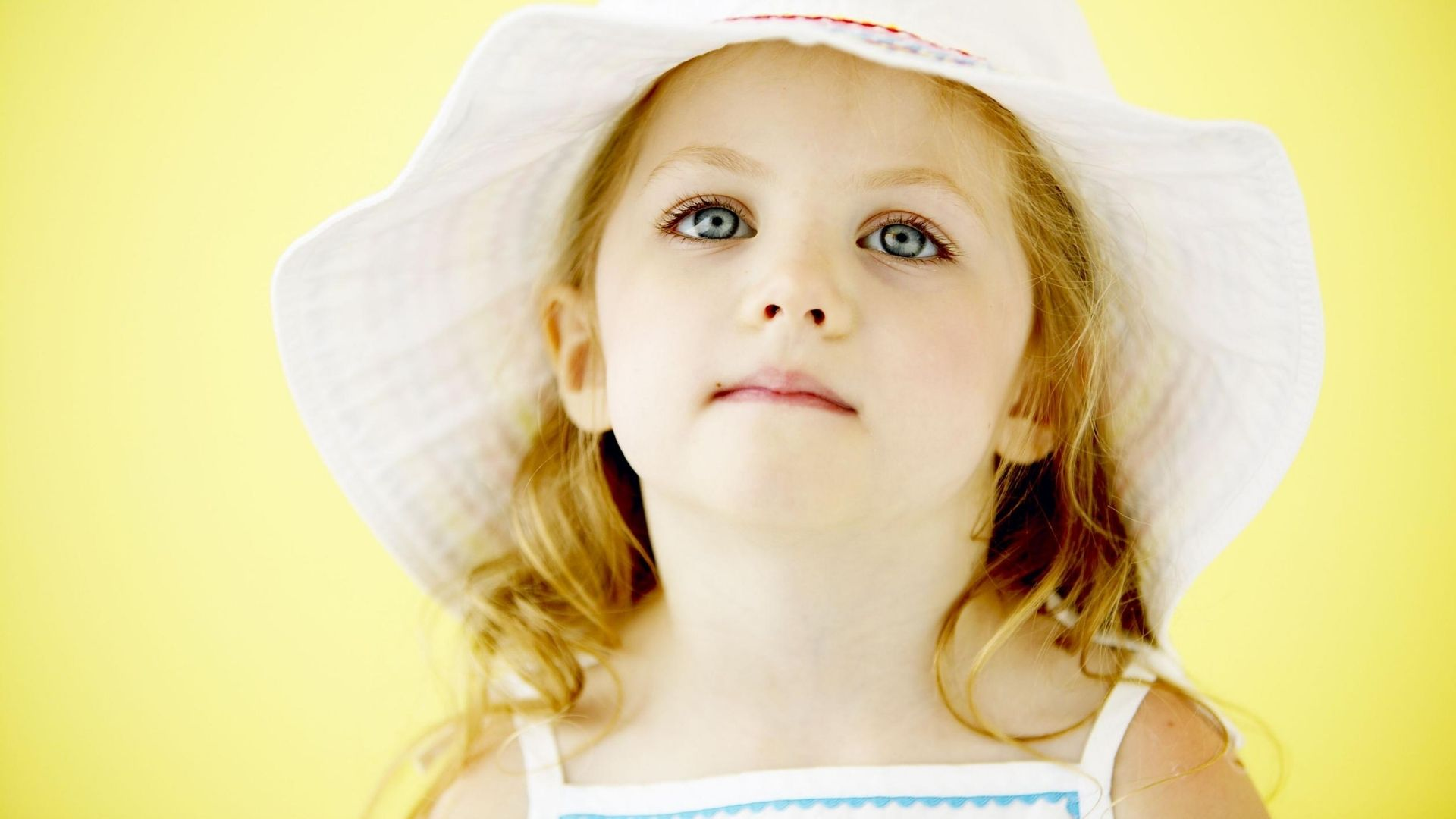 Young girl wearing a floppy hat.