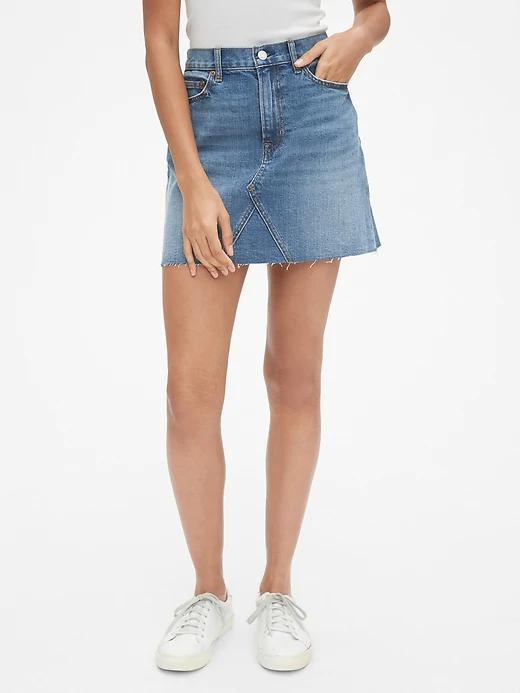 A model wearing a denim skirt. This style is a mini skirt in denim.