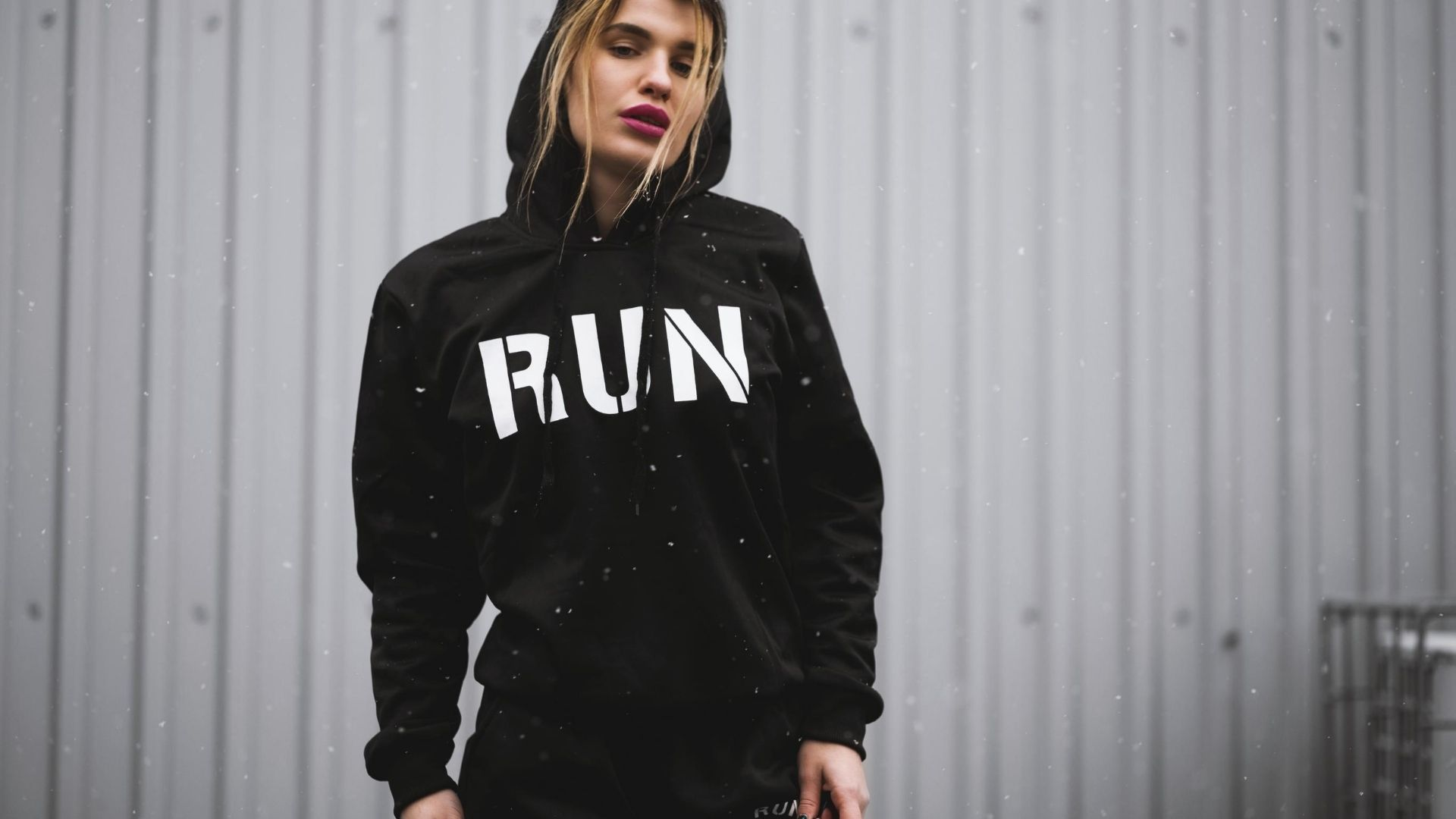 Woman wearing a black hoodie with the word 'run' written across the front.