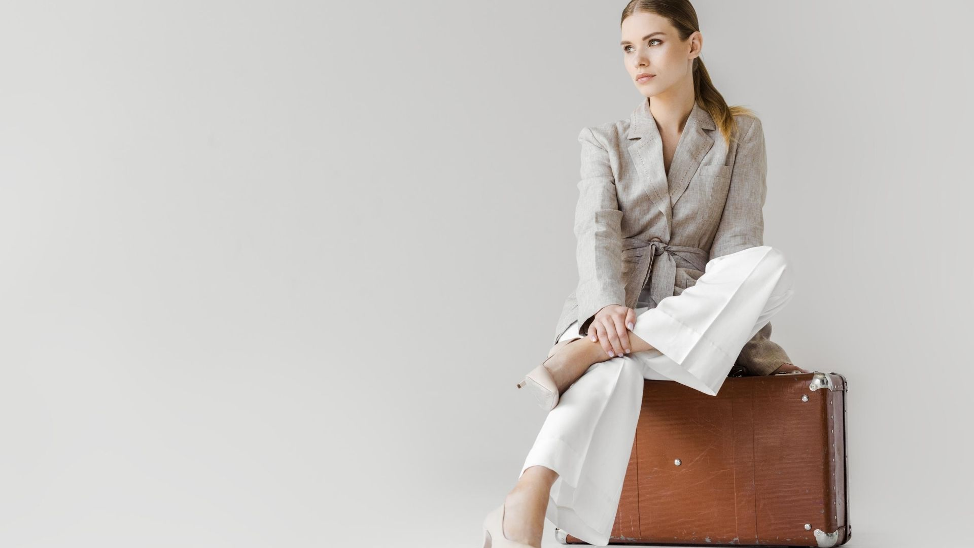 Woman wearing a linen jacket sits on a battered suitcase.