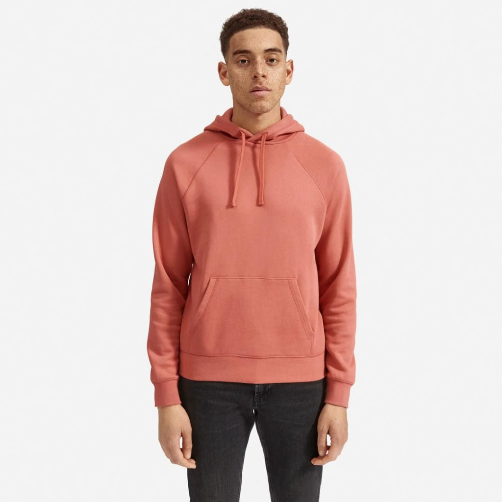 Man in a pink hoodie with front pockets and drawstrings.