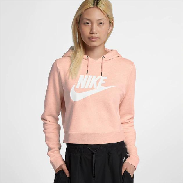 Woman in pink crop top hoodie with Nike logo to the front.