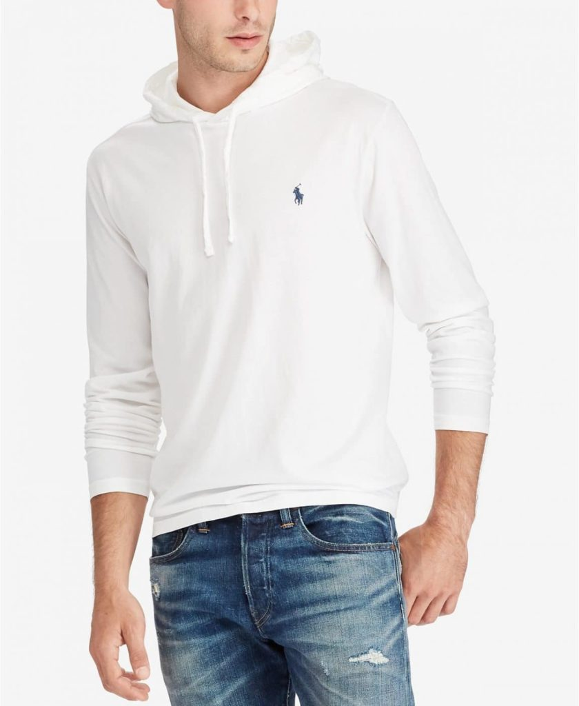 Male model wearing a white polo hoodie and blue jeans.