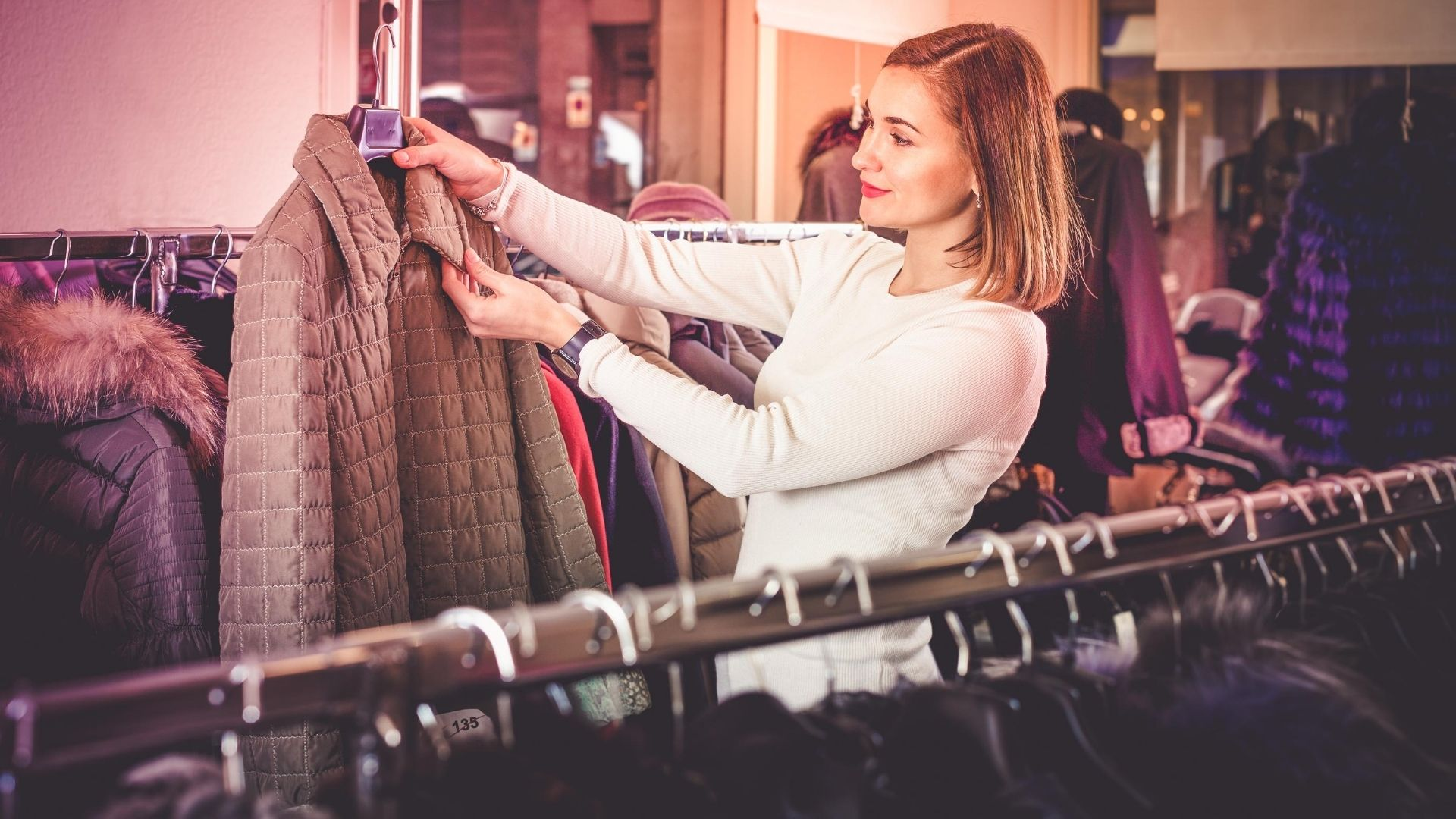 Woman holding up a quilted jacket in the jacket/coat section of a store.