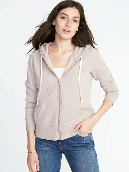 Woman in cream zip-up hoodie with front pockets and drawstrings.