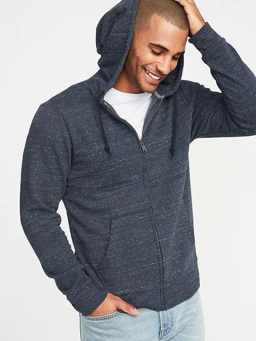 Man in a zip-front hoodie with drawstrings and front pockets.