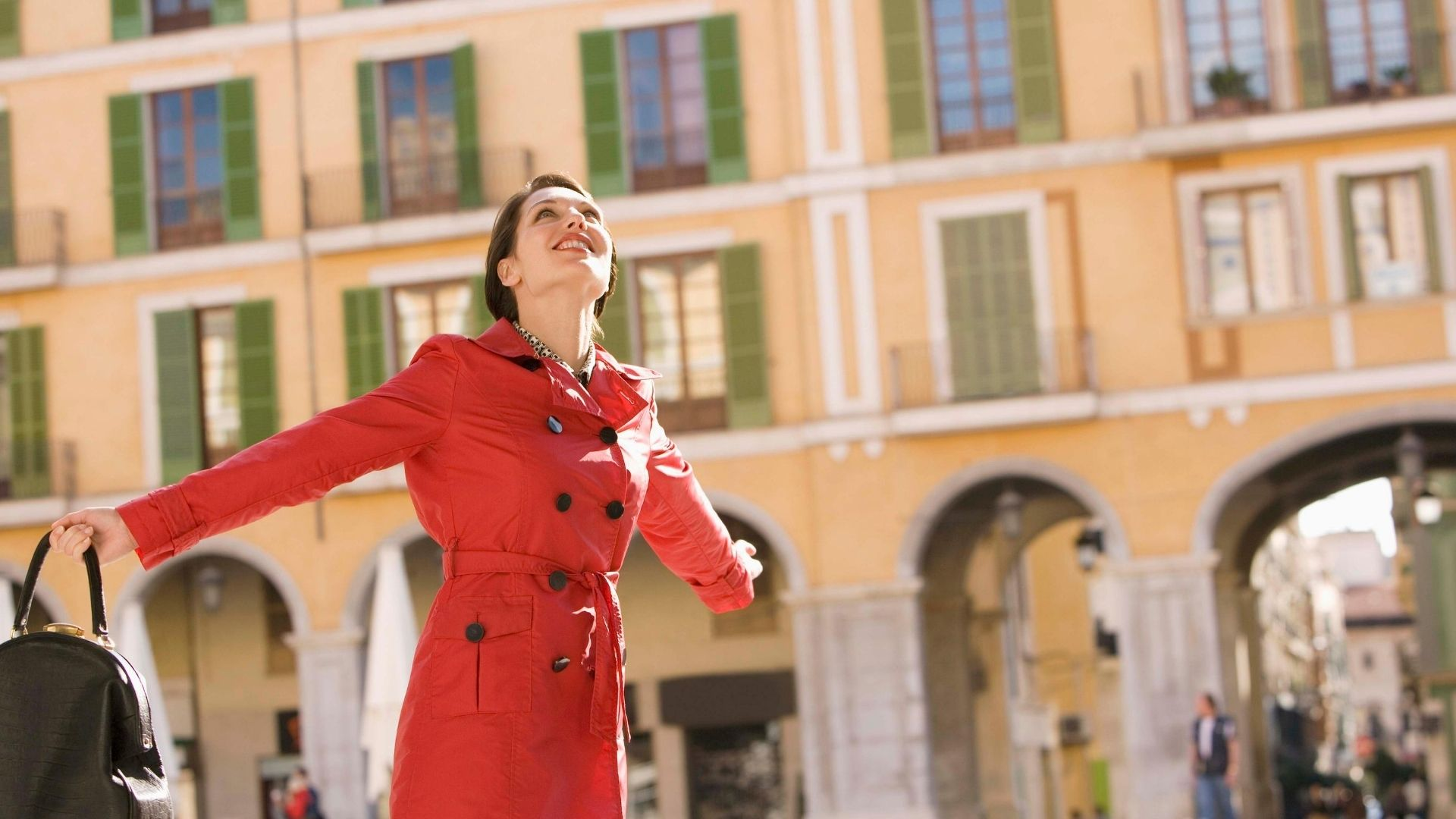 Woman wearing a red trench coat stretches out her arms and looks up to the sky with a smile on her face.