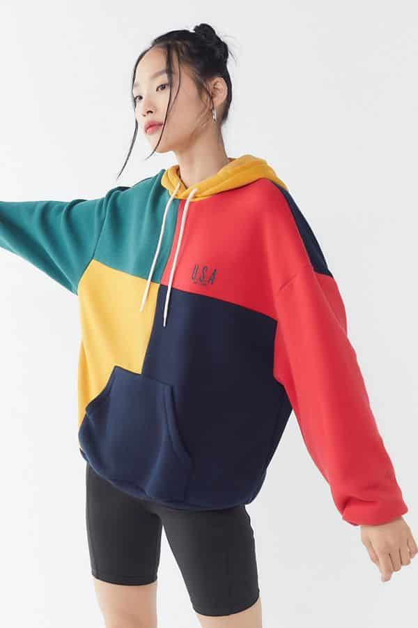 Woman in multicolored over-sized hoodie with front pockets and drawstrings.