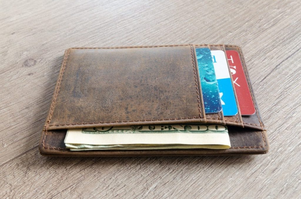 Brown leather card case wallet laid out on plywood with cards and money in the pockets.