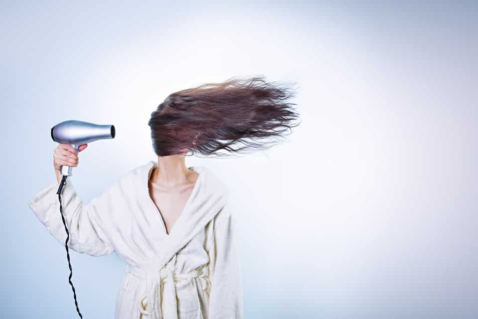 Woman with blow dryer. Blowdrying perm.