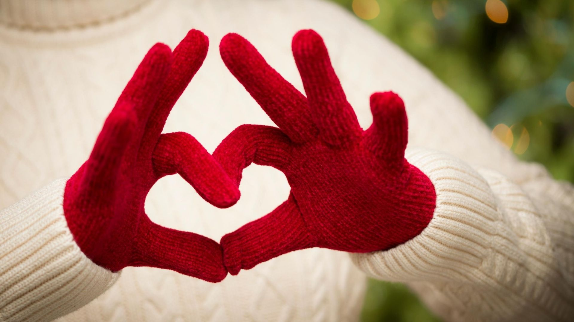 Woman wearing  red Christmas mittens.