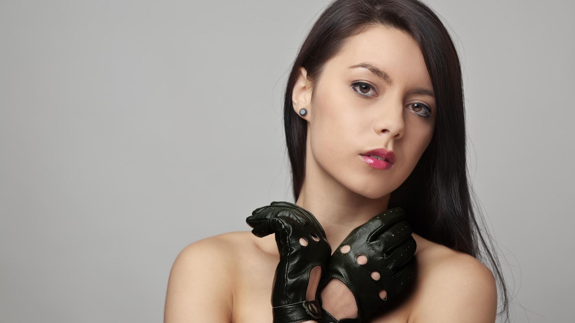 Woman wearing a pair of black driving gloves.