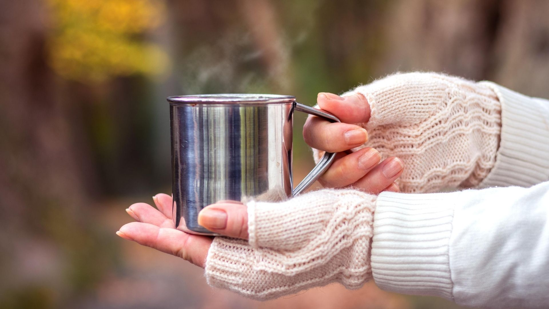 Woman wearing a pair of fingerless gloves holds a hot tin cup of tea.