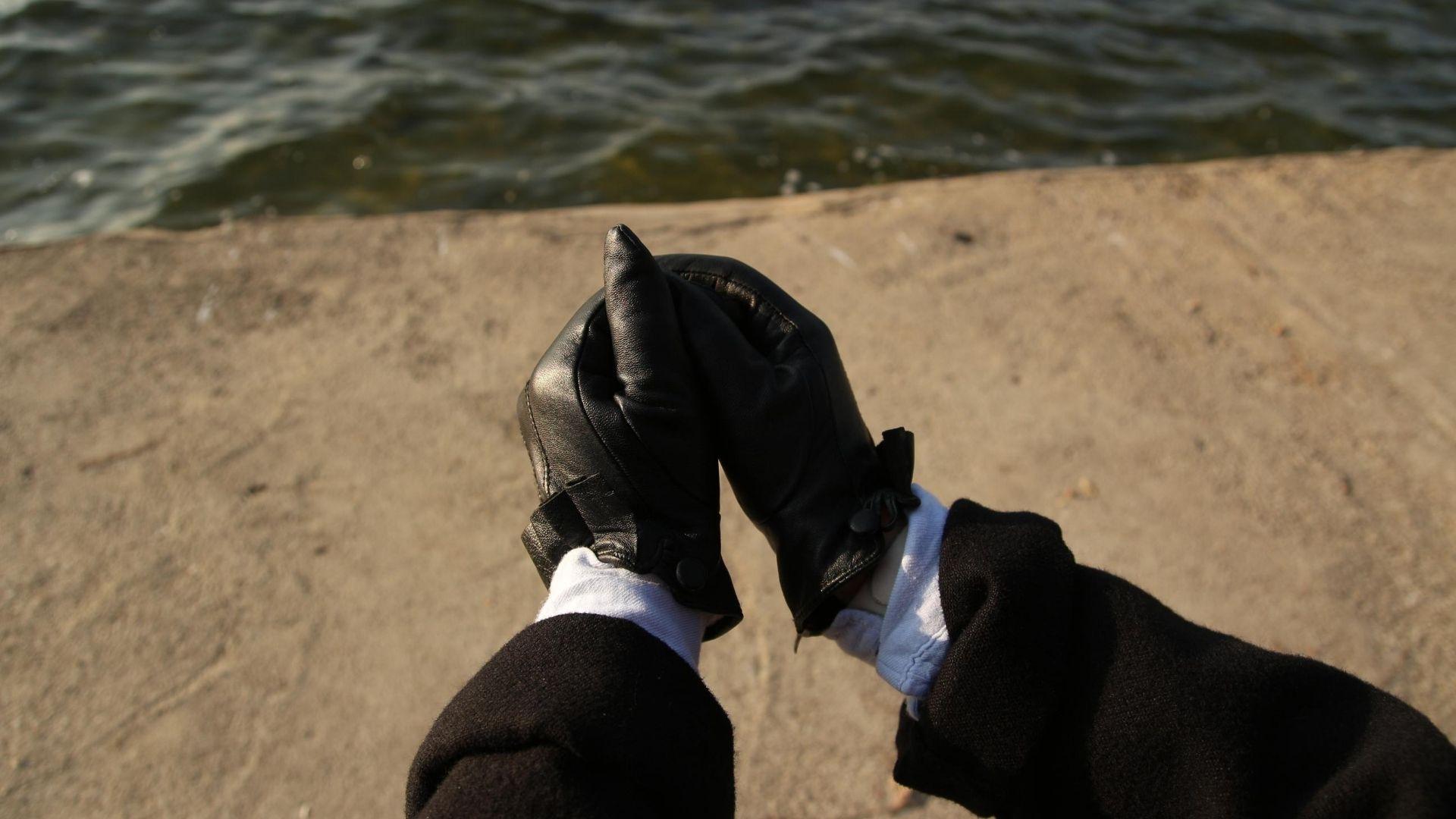 Woman wearing stylish black leather gloves.